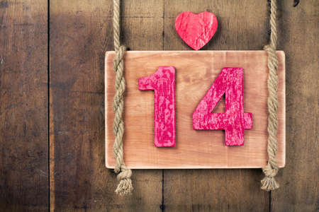 Valentine heart shape, wood frame and number fourteen with rope hanging on planks background photo
