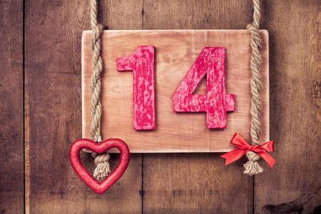 Fourteen valentine card, heart hanging on wooden planks background Stock Photo - 17627866