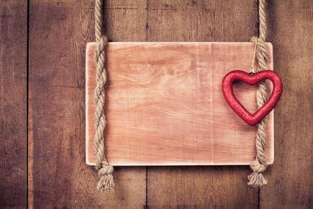 Valentine hart, houten frame met touw opknoping op planken achtergrond