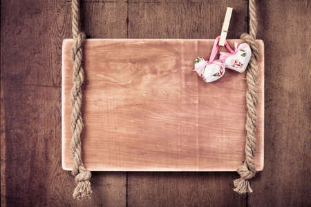 Wooden Valentine background with hearts hanging on rope photo