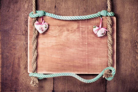 Vintage Valentine frame background with hearts hanging on rope photo