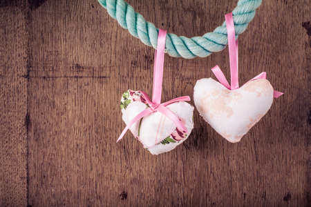 Vintage Valentine wooden background with hearts hanging on rope photo