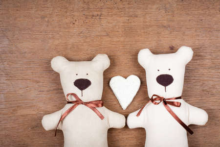 Valentine card with handmade bears and heart on wooden texture photo