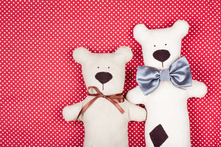 homemade style: Handmade pair of bears on red textile texture background