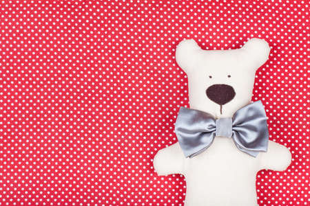 Handmade toy bear on red and white textile photo