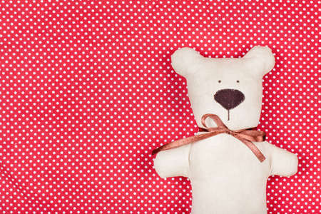 Toy bear on red and white cotton background photo