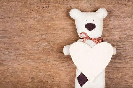 Valentijn kaart met handgemaakte beer en hart op houten textuur