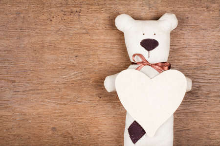 Valentine card with handmade bear and heart on wooden texture