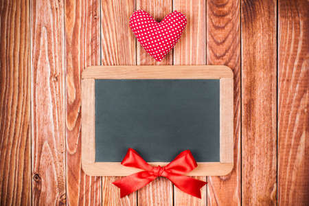 Valentine card with heart, signboard and red bow on wooden background photo