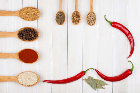 Recipe notebook, spices in wooden spoons on white wood background photo