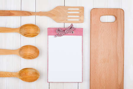 Recipe notebook, kitchen equipment on white wood background photo