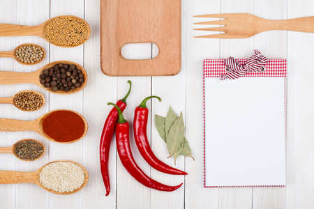 paprika: Recipe notebook, spices in wooden spoons on white wood background