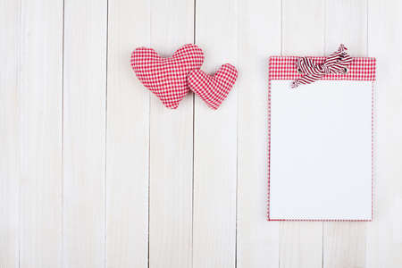 Notebook and hearts on white wood background