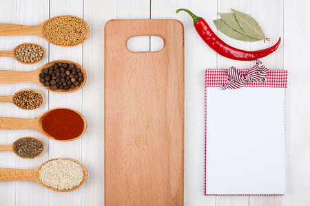 cookbook: Recipe notebook, spices in wooden spoons on white wood background