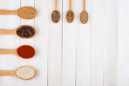 Spices in wooden spoons on white wood background