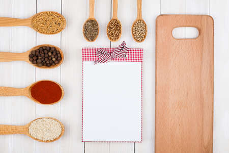 Recipe notebook, spices in wooden spoons on white wood background
