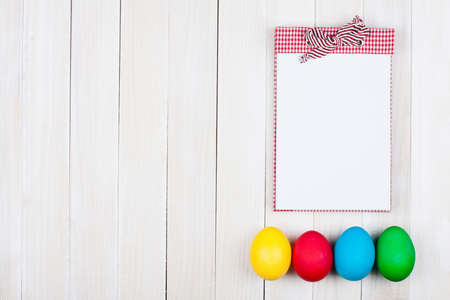 Easter eggs and notebook on white wood background photo