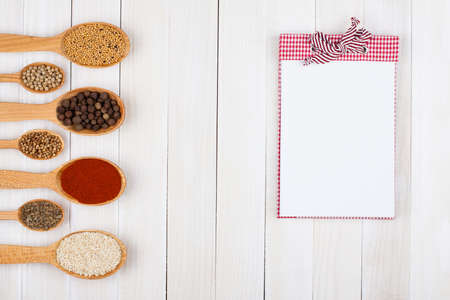 simple meal: Recipe notebook, spices in wooden spoons on white wood background
