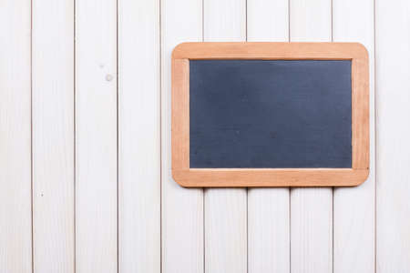 Blackboard on wooden wall background photo