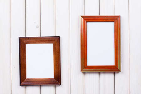 Frames on white wooden wall background