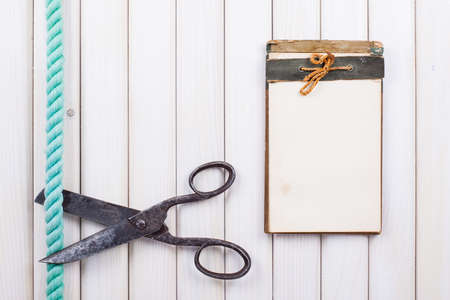 Notebook, old scissors, rope on white wood background photo