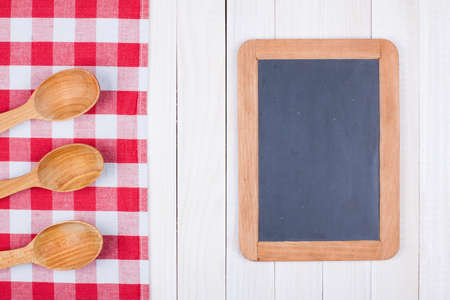 Blackboard, kitchen equipment on white wood background
