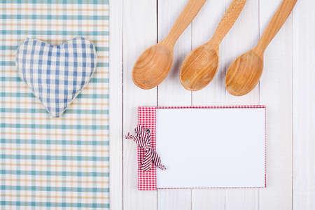 Recipe notebook, kitchen equipment on white wood background photo