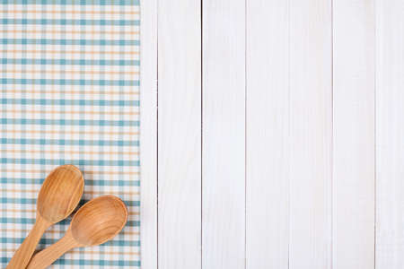recipe card: Tablecloth, wooden spoons on wood textured background Stock Photo