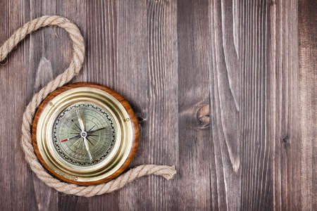 Big vintage compass and rope on wooden texture background photo
