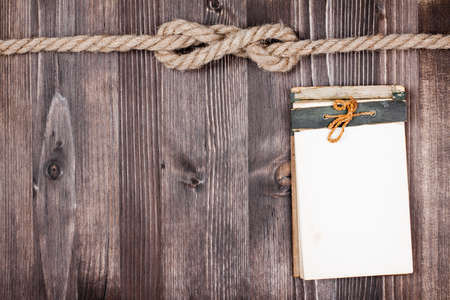 notebook cover: Antique Old Grunge notebook, Rope knot on wooden background Stock Photo