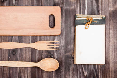 Old Recipe notebook, kitchen plank, spoon, fork on wood background