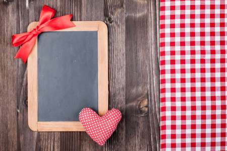 Love Valentine heart and blackboard, tablecloth on wooden background photo
