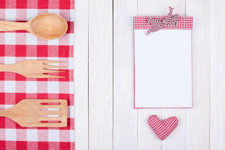 Recipe notebook, kitchen equipment on white wood background