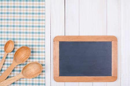 Blackboard, spoons on white wood background photo