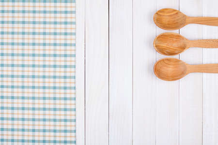Tablecloth, wooden spoons on wood textured background Standard-Bild