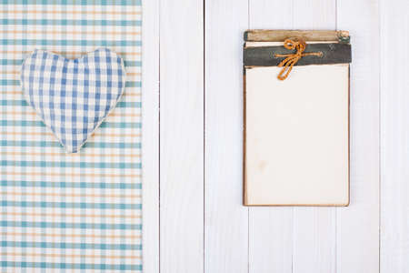 Vintage Notebook, tablecloth, heart on white wooden table