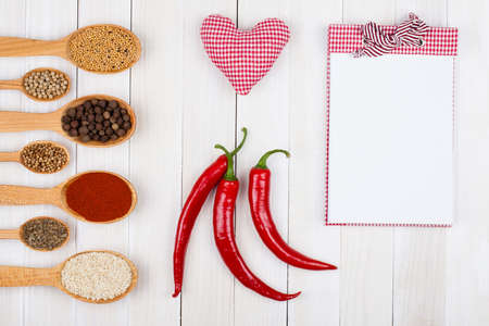 Recipe book, spices in spoons, chili, heart on wood background photo