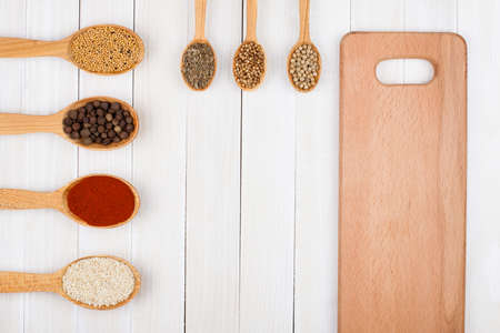 Spices in wooden spoons on white wood background photo
