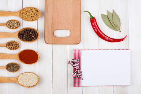 Cooking recipe notebook, chili, spices on white wood photo