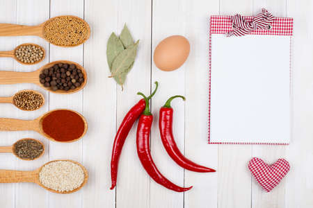Spices, recipe notebook on white wood background photo