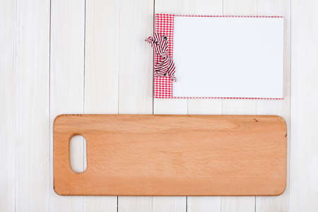 Recipe book, kitchen board on white wood background photo