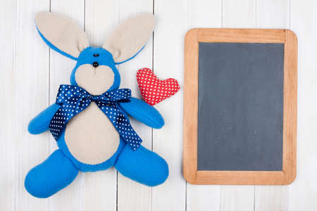 Bunny, heart, blackboard on white wood background photo