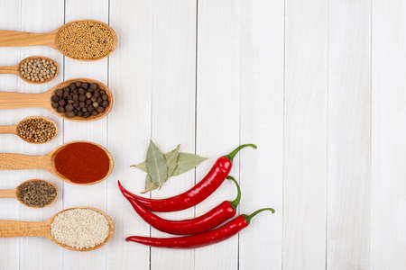 Chili, spices in wooden spoons on wood background photo