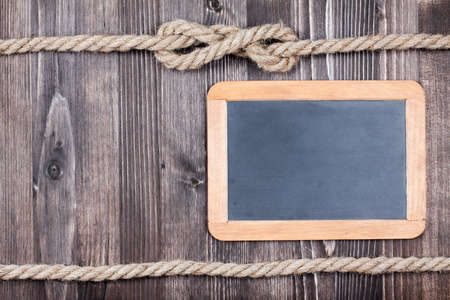 Black board on wooden planks with rope background