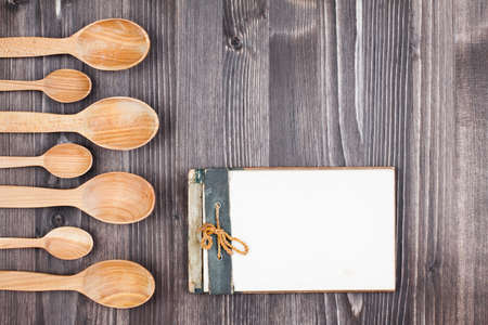 Recipe cook book, spoons on wood background