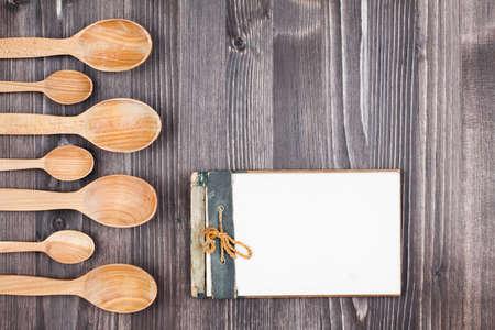 Libro di cucina Ricetta, cucchiai su sfondo di legno Archivio Fotografico