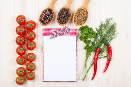 Recipe notebook, chili, cherry tomatoes, spices on white wood background photo
