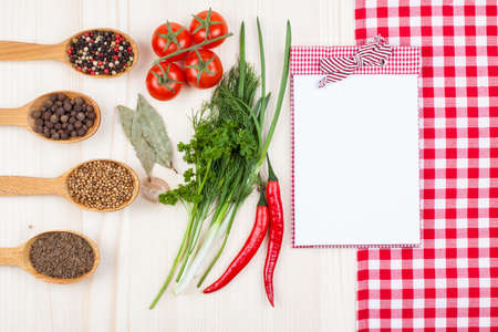 Recipe cook book, chili, cherry tomatoes, spices, red and white tablecloth on wood background photo