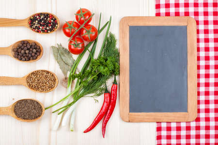 Recipe or menu chalk board, chili, cherry tomatoes, spices, tablecloth on wood background photo