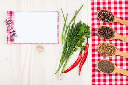 red tablecloth: Recipe cook book, chili, spices, red and white tablecloth on wood background